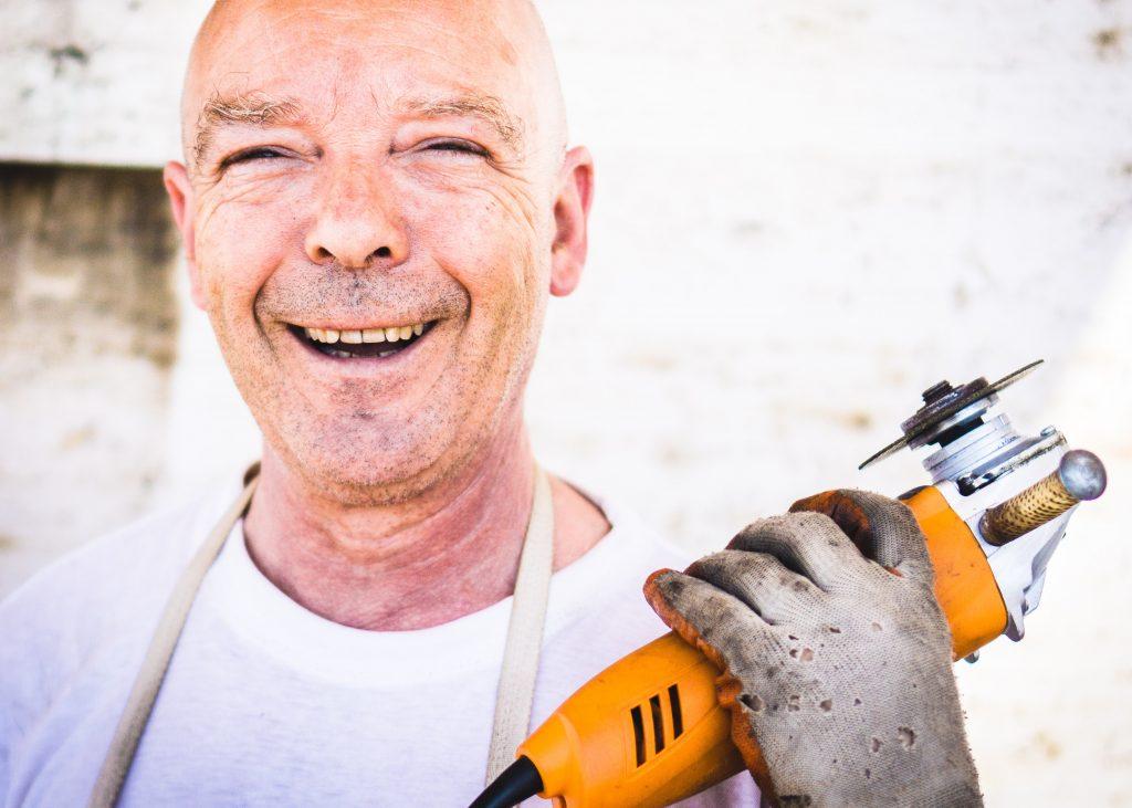 Uśmiechnięty mężczyzna trzymający narzędzie,