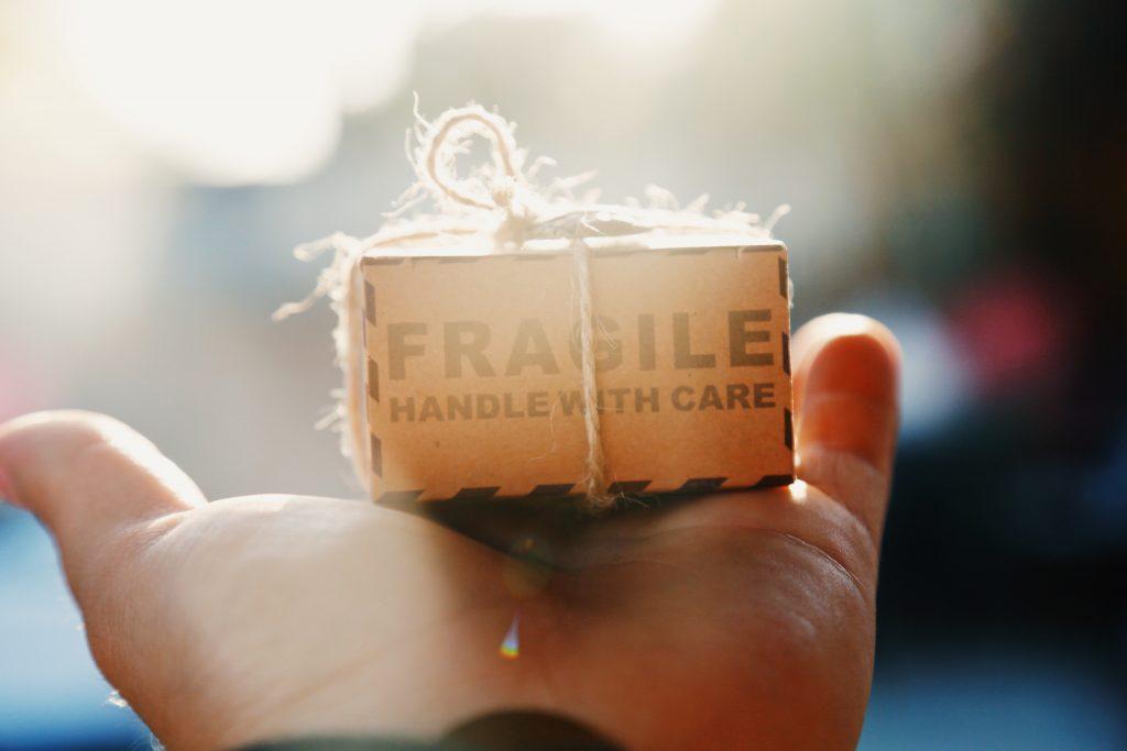 małe pudełko z przesyłką trzymane w dłoni