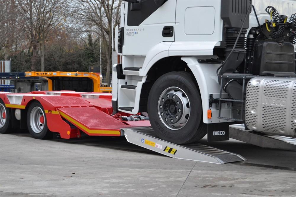 Biały samochód ciężarowy wjeżdżający na rampy aluminiowe