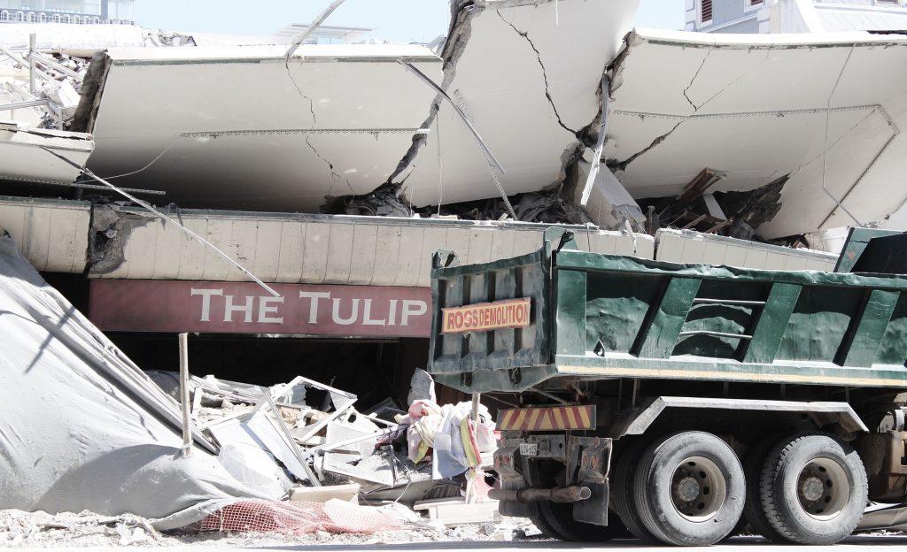 samochód ciężarowy i zburzony budynek