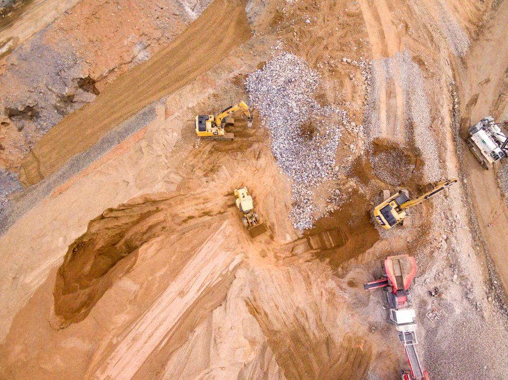 Koparki przy pracy na piaszczystej budowie z góry