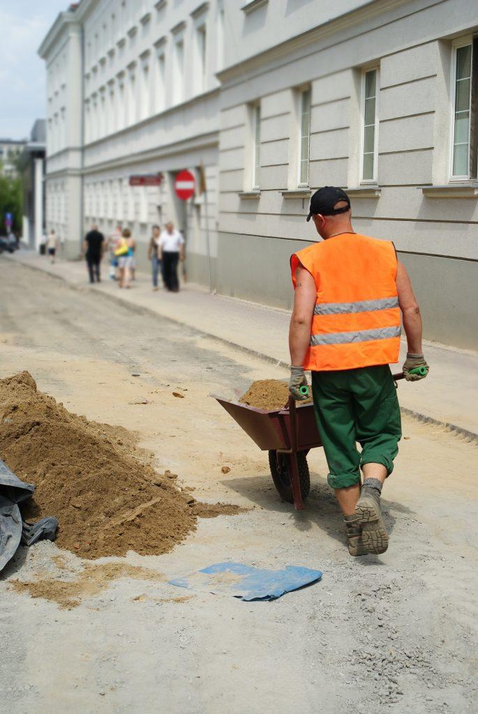 Robotnik tyłem idący ulicą z taczką z piaskiem, w tle przechodnie.