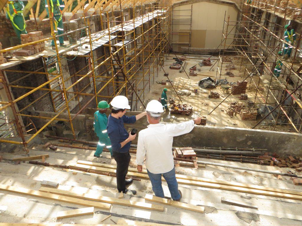 Teren budowy, rusztowania, robotnicy i dwóch mężczyzn w białych kaskach