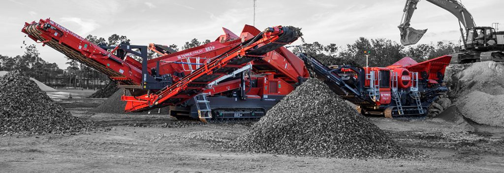 Czerwone maszyny budowlane przerzucają żwir