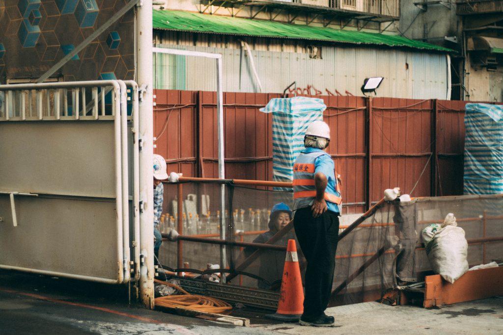 Pracujący robotnicy - remont maszyny budowlanej