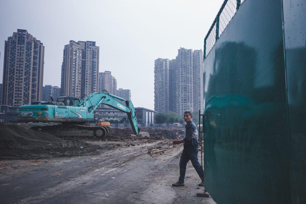 Człowiek na budowie drogowej i niebieska koparka gąsienicowa